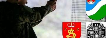 Zdjęcie człowieka na strzelnicy herb powiatu, herb Augustowa, logo Stowarzyszenia Augustowscy Strzelcy, logo POW
